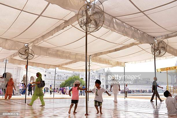 Indian Sikh children play under fans in the scorching heat as they come to pay their respects at the Sikh Shrine Golden temple in Amritsar on June 18...
