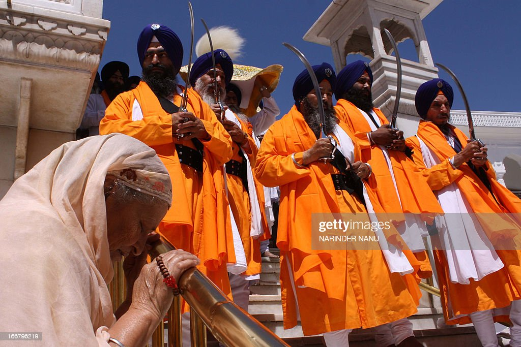 Indian Sikh devotee prays as Sikh warriors known as Punj Pyara hold swords during a procession from the Sri Akal Takhat at the Sikh Shrine to the Golden Temple in Amritsar on April 17, 2013, on the eve of the 392nd birth anniversary of the ninth Sikh Guru, Teg Bahadur. Guru Tegh Bahadur, the youngest of the five sons of Guru Hargobind, was born in Amritsar in 1621 and was executed on the orders of Mughal Emperor Aurangzeb in Delhi in 1675.