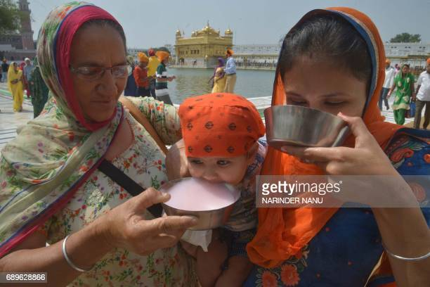 Indian Sikh devotees and a baby drink sweet water distributed by volunteers at the Golden Temple in Amritsar on May 29 2017 Sikh devotees are marking...