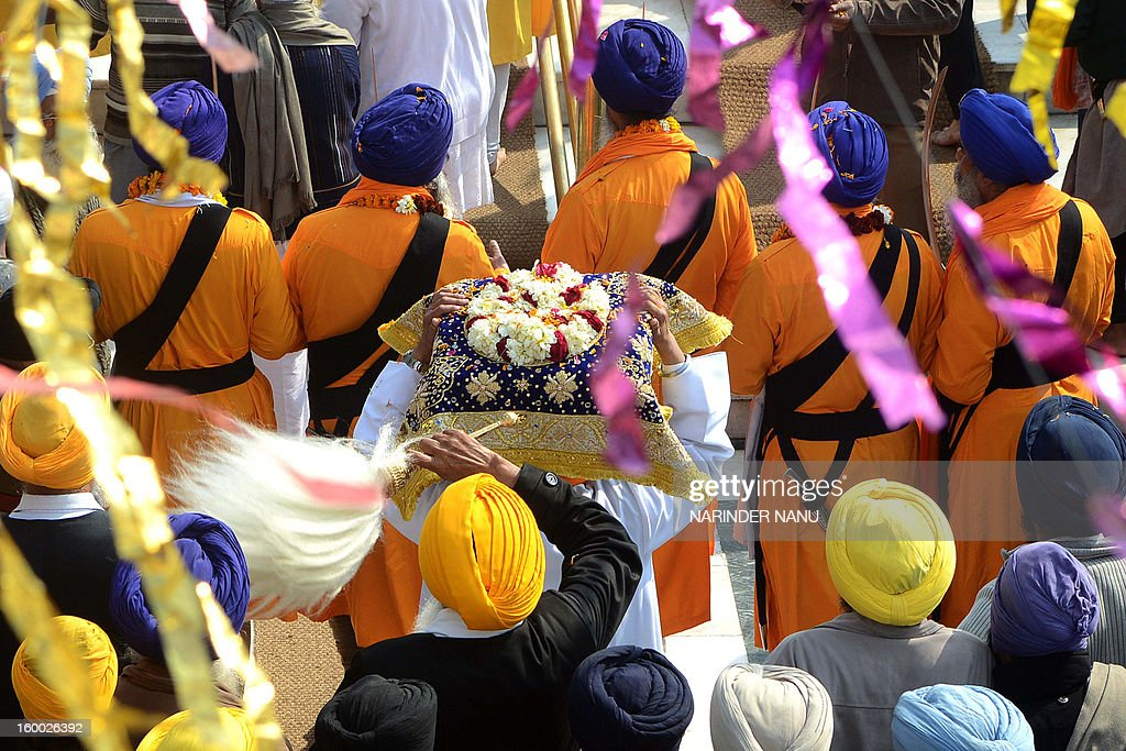 Indian Sikh devotees and holy men known as 'Punj Pyara' hold swords as they escort Sikh priest Jagtar Singh (C) as he carries the Sikh Holy Book - Guru Granth Sahib - during a procession at the Golden Temple in Amritsar on January 25, 2013 on the eve of the 331th Birth Anniversary of Sikh warrior, Shaheed Baba Deep Singh. The Gurdwara Shaheed Bunga Baba Deep Singh at the Golden Temple commemorates the memory of Singh and his great deeds.