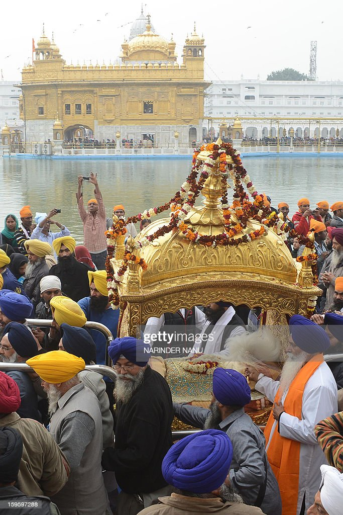 Indian Sikh devotees carry the Guru Granth Sahib (Sikh Holy Book) on a palanquin during a procession from The Sri Akal Takhat at The Golden Temple in Amritsar on January 17, 2013. The procession took place on the eve of the 348th Birth Anniversary of tenth Sikh Guru Gobind Singh.