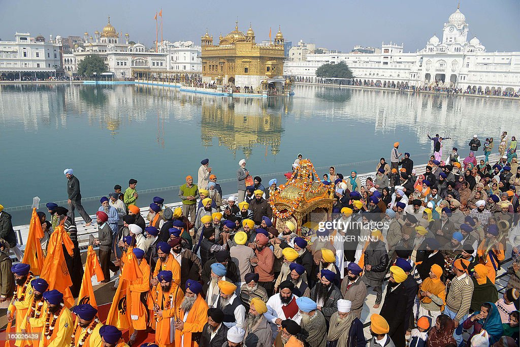 Indian Sikh devotees carry the Palki Sahib - Sikh Holy Book - Guru Granth Sahib - during a procession at the Golden Temple in Amritsar on January 25, 2013 on the eve of the 331th Birth Anniversary of Sikh warrior, Shaheed Baba Deep Singh. The Gurdwara Shaheed Bunga Baba Deep Singh at the Golden Temple commemorates the memory of Singh and his great deeds.