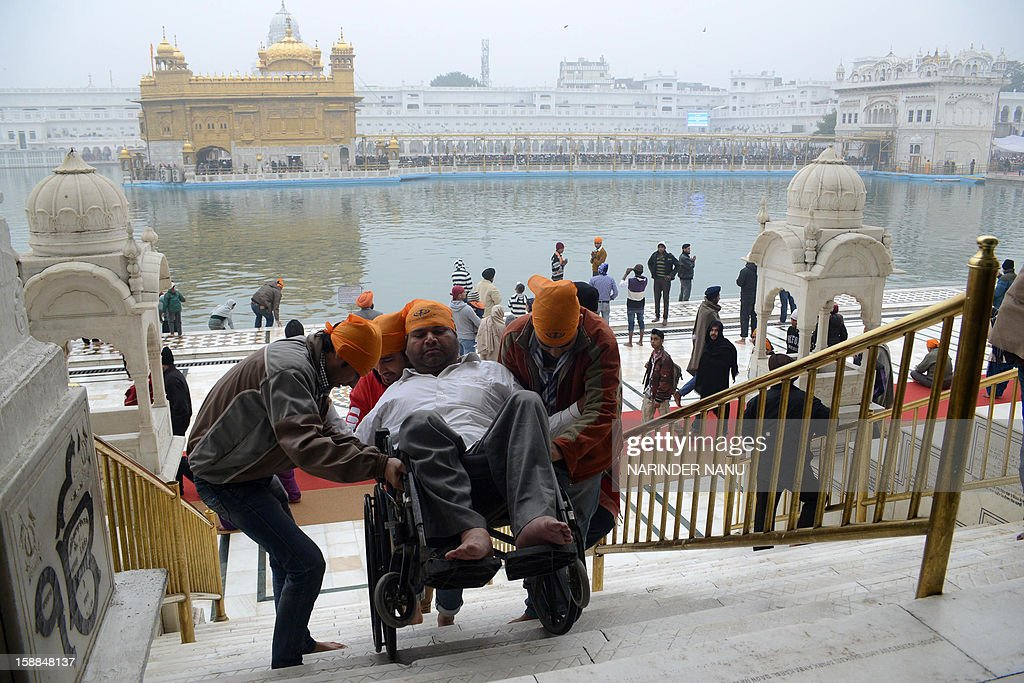 Indian Sikh devotees helps a physically challenged devotee as they arrive to pay homage at the Sikh Shrine Golden Temple in Amritsar on January 1, 2013. Thousands of Sikh devotees from across India and abroad are preparing to pay obeisance on the occasion of New Year at the temple in northern India.