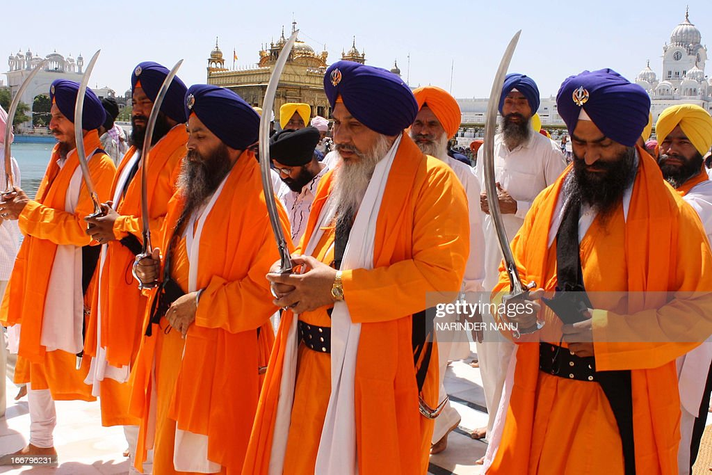 Indian Sikh devotees known as Punj Pyara hold swords during a procession from the Sri Akal Takhat at the Sikh Shrine to the Golden Temple in Amritsar on April 17, 2013, on the eve of the 392nd birth anniversary of the ninth Sikh Guru, Teg Bahadur. Guru Tegh Bahadur, the youngest of the five sons of Guru Hargobind, was born in Amritsar in 1621 and was executed on the orders of Mughal Emperor Aurangzeb in Delhi in 1675.