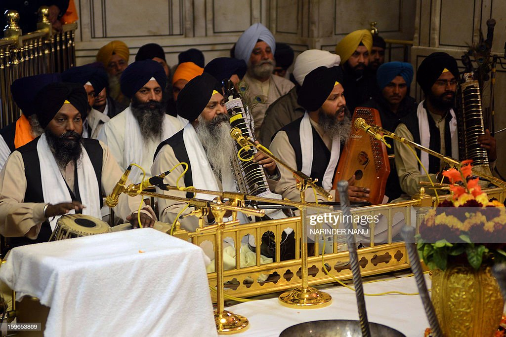 Indian Sikh devotees known as Ragi-group perform Shabad Kirtan in the front of the Guru Granth Sahib, the Holy Book of Sikhism inside the Sikh Shrine Golden Temple in Amritsar on January 18, 2013. Sikhs are celebrating the 348th Birth Anniversary of the tenth Sikh Guru Gobind Singh.