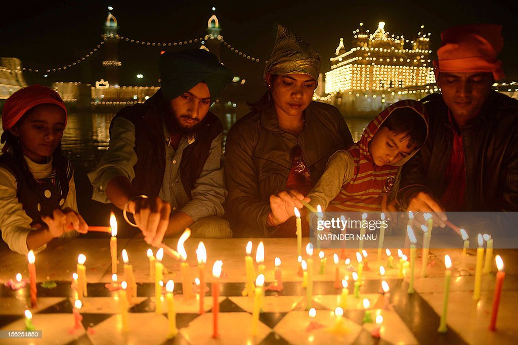 Indian Sikh devotees light candles as they pay their respects at the illuminated Sikhism's holiest shrine Golden Temple in Amritsar on November 12, 2012, on the eve of Bandi Chhor Divas or Diwali. Sikhs celebrate Bandi Chhor Divas or Diwali to mark the return of the Sixth Guru, Guru Hargobind Ji, who was freed from imprisonment and also managed to release 52 political prisoners at the same time from Gwalior fort by Mughal Emperor Jahangir in 1619.