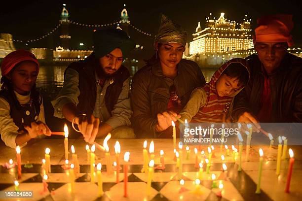 Indian Sikh devotees light candles as they pay their respects at the illuminated Sikhism's holiest shrine Golden Temple in Amritsar on November 12 on...