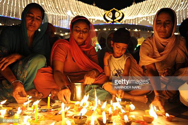Indian Sikh devotees light candles as they pay their respects at the Golden Temple on the occasion of Bandi Chhor Divas or Diwali in Amritsar on...