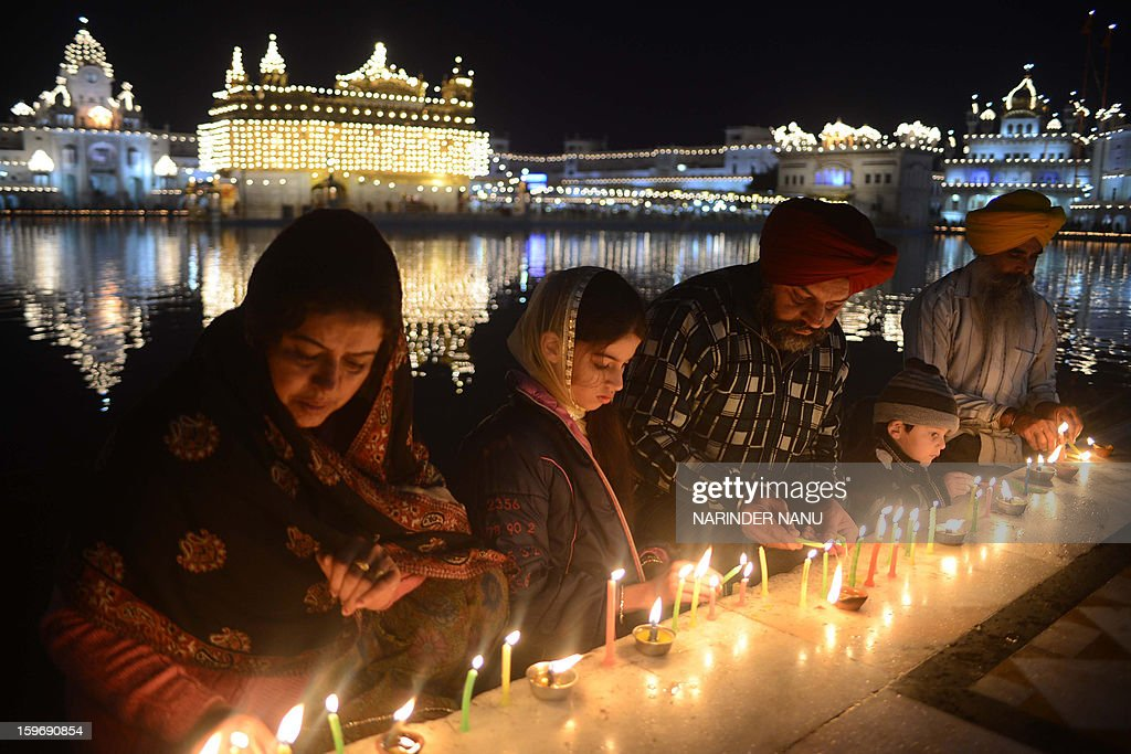 Indian Sikh devotees light candles at the Golden Temple in Amritsar on January 18, 2013. Sikhs are celebrating the 348th Birth Anniversary of the tenth Sikh Guru Gobind Singh.