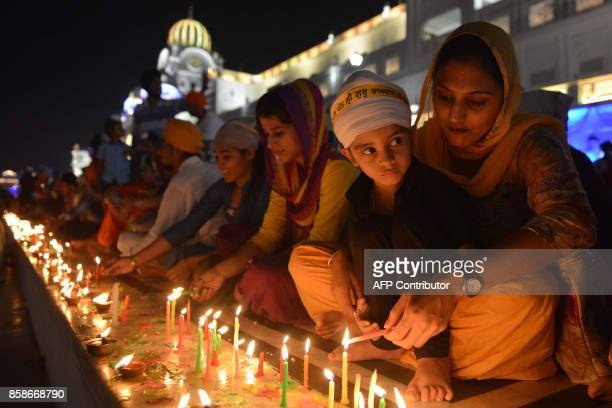 Indian Sikh devotees light candles on the occasion of the birth anniversary of the fourth Sikh Guru Ram Das at the Golden Temple in Amritsar on...