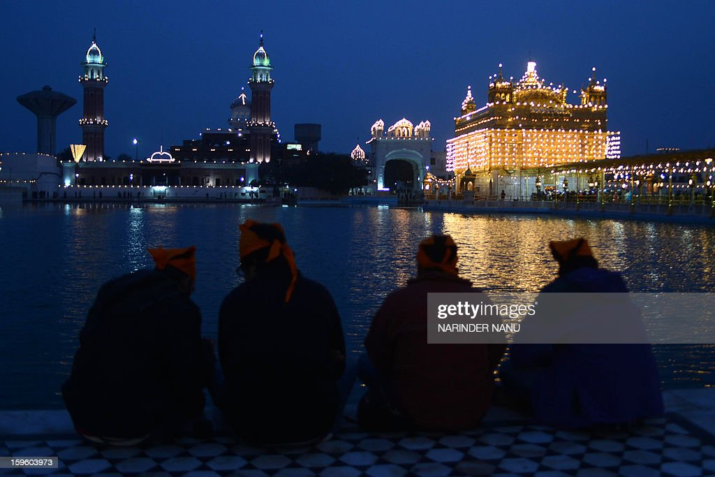 Indian Sikh devotees pay their respects at the illuminated Golden Temple in Amritsar on January 17, 2013, on the eve of the 348th Birth Anniversary of tenth Sikh Guru Gobind Singh. AFP PHOTO/NARINDER NANU