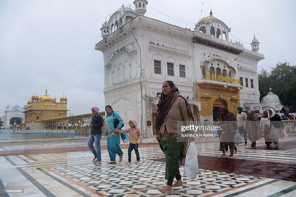 Indian Sikh devotees pay their respects during a rain shower at the Sikh Shrine Golden Temple in Amritsar on January 18, 2013. Sikhs are celebrating the 348th Birth Anniversary of the tenth Sikh Guru Gobind Singh.