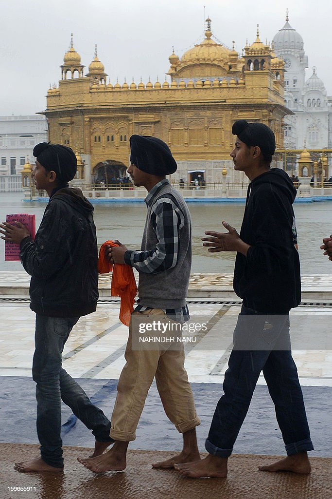 Indian Sikh devotees pay their respects during a rain shower at the Sikh Shrine Golden Temple in Amritsar on January 18, 2013. Sikhs are celebrating the 348th Birth Anniversary of the tenth Sikh Guru Gobind Singh. AFP PHOTO/NARINDER NANU