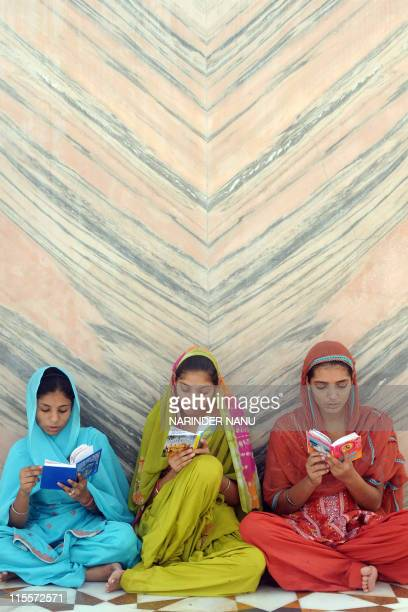Indian Sikh devotees read the Nitnem Gutka holy book at the Sikh shrine the Golden temple in Amritsar on June 5 2011 Indian Sikh's celebrated the 405...