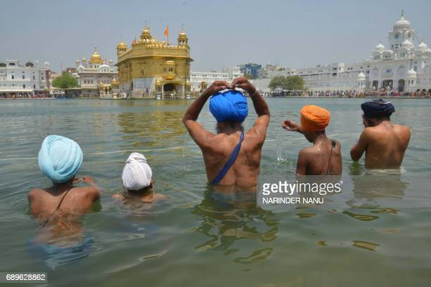 Indian Sikh devotees take a dip in the holy sarovar at the Golden Temple in Amritsar on May 29 2017 Sikh devotees are marking the 411th Martyrdom Day...