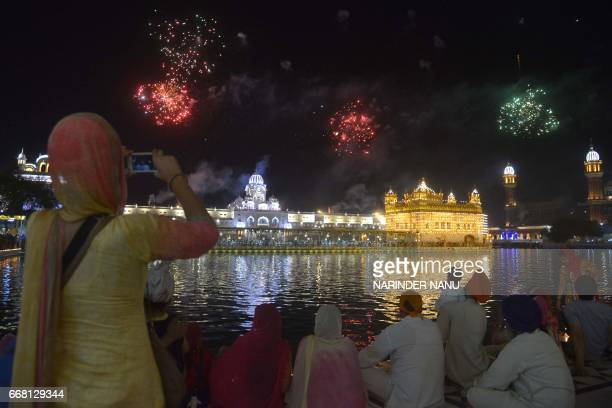 Indian Sikh devotees watch a fireworks display on the occasion of the Baisakhi festival at the illuminated Golden Temple in Amritsar on April 13 2017...