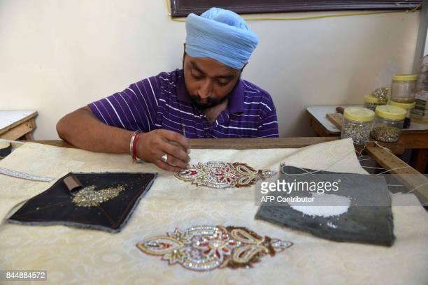 Indian Sikh Gurdev Singh embroider wroks on a wedding dress 'Sherwani' for groom at a studio boutique in Amritsar on September 9 2017 / AFP PHOTO /...