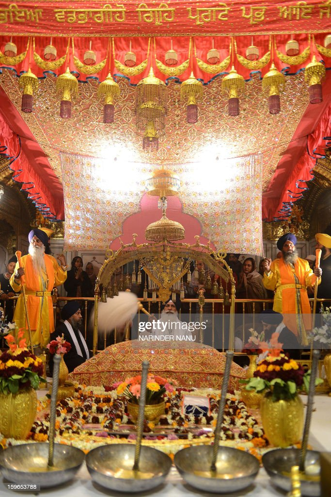 Indian Sikh head priest Mal Singh (C) sits behind the Guru Granth Sahib, the Holy Book of Sikhism inside the Sikh Shrine Golden Temple in Amritsar on January 18, 2013. Sikhs are celebrating the 348th Birth Anniversary of the tenth Sikh Guru Gobind Singh.