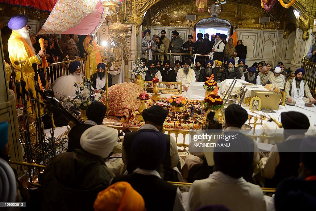 Indian Sikh head priest Mal Singh (2L) sits behind the Guru Granth Sahib, the Holy Book of Sikhism inside the Sikh Shrine Golden Temple in Amritsar on January 18, 2013. Sikhs are celebrating the 348th Birth Anniversary of the tenth Sikh Guru Gobind Singh.