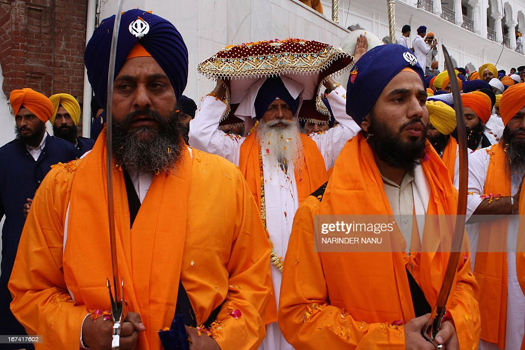 Indian Sikh holy men, known as Punj Pyara, hold swords as they escort head priest Mal Singh (C) as he carries the Guru Granth Sahib (Sikh Holy Book) during the inauguration ceremony of a memorial at the Golden Temple in Amritsar on April 25, 2013, for the Sikh devotees that died in 1984 in Operation Blue Star. Operation Blue Star took place from the 3–6 June 1984 and was an Indian military operation, ordered by Indira Gandhi, then Prime Minister of India to remove Sikh separatists from the Golden Temple in Amritsar. AFP PHOTO/ NARINDER NANU