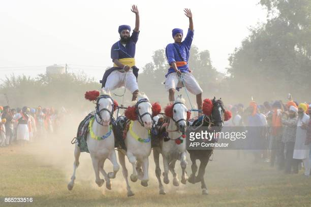Indian Sikh 'Nihangs' or traditional Sikh army members demonstrate riding skills during celebrations to mark Fateh Divas which takes place the day...