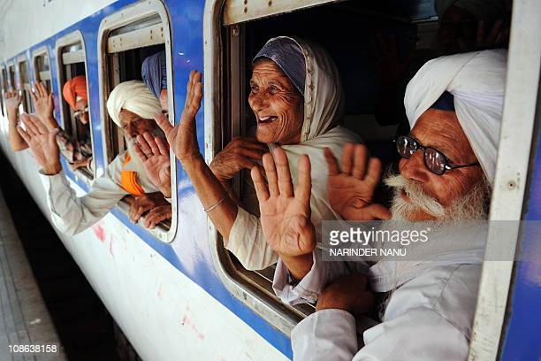 Indian Sikh pilgrims wave after boarding a train for Pakistan at a railway station in Amritsar on April 11 2010 Thousands of Indian Sikh pilgrims...