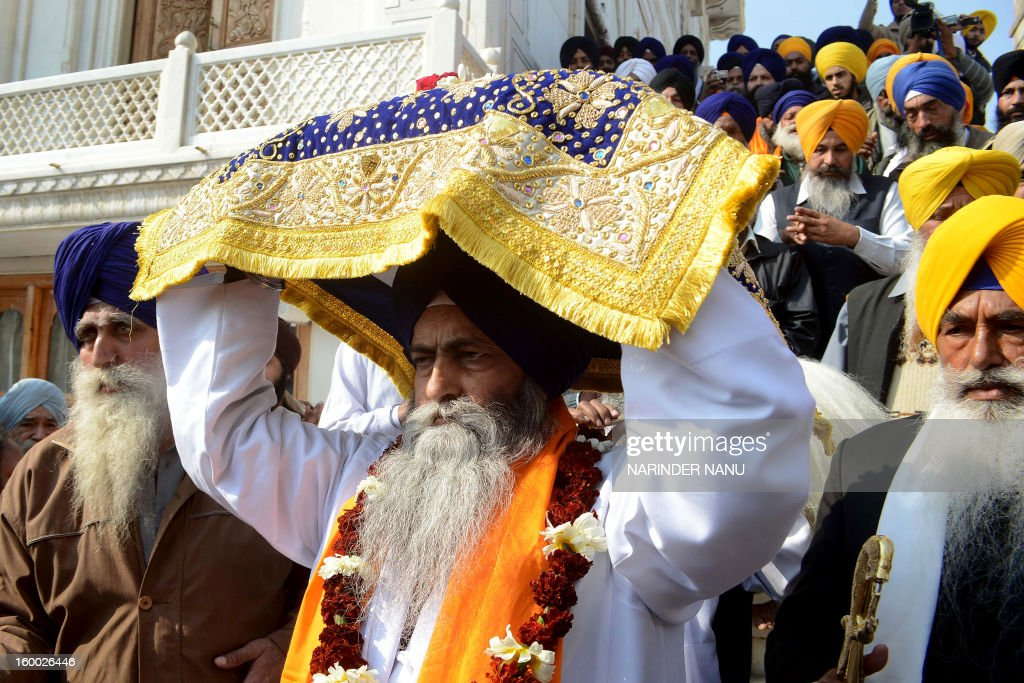 Indian Sikh priest Jagtar Singh (C) carries the - Sikh Holy Book - Guru Granth Sahib - during a procession at the Golden Temple in Amritsar on January 25, 2013 on the eve of the 331th Birth Anniversary of Sikh warrior, Shaheed Baba Deep Singh. The Gurdwara Shaheed Bunga Baba Deep Singh at the Golden Temple commemorates the memory of Singh and his great deeds.