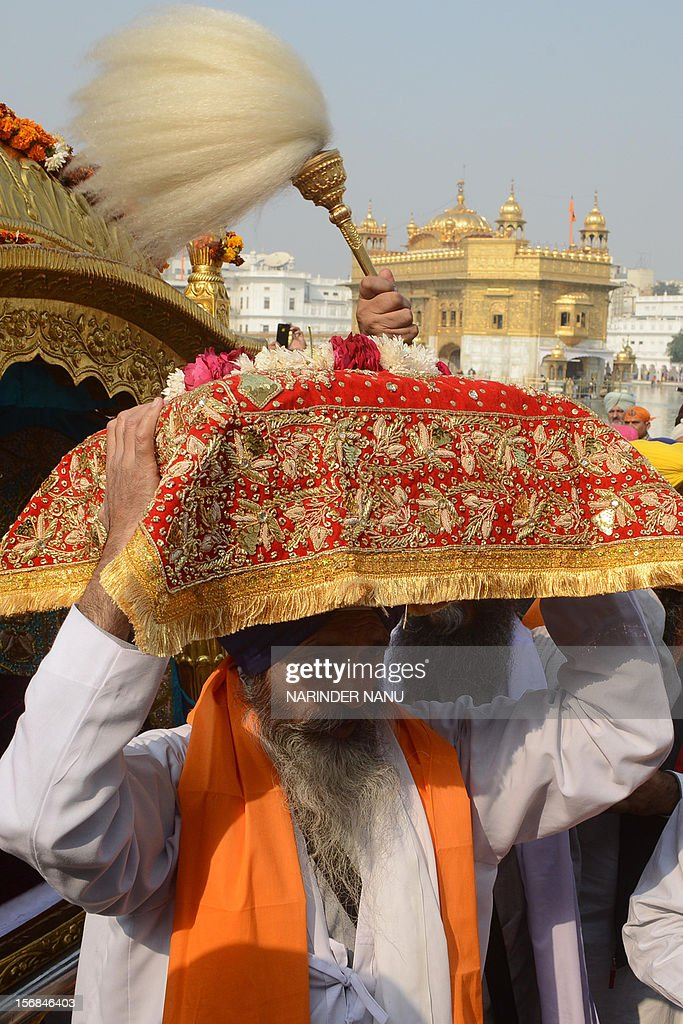 Indian Sikh priest Ravel Singh (C) carries The Guru Granth Sahib (Sikh Holy Book) during a procession at The Sikh Shrine Golden Temple in Amritsar on November 23, 2012, on the eve of the Martyrdom Anniversary of the Ninth Guru of Sikhism, Sri Guru Teg Bahadur. Sri Guru Tegh Bahadur Sahib was born at Amritsar in 1621 and was the youngest son of Sri Guru Hargobind Sahib. He adorned the Sacred Throne of Sri Guru Nanak Sahib from 1664 to 1675.