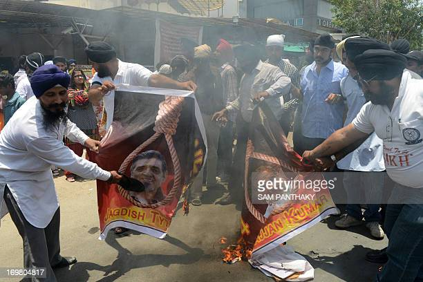 Indian Sikhs burn posters depicting the images of Congress leaders Jagdish Tytler and Sajjan Kumar during a rally seeking justice for the massacre of...