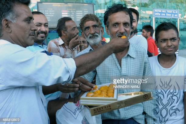 Indian Sikhs evacuated from flooding in Srinagar are fed sweets as they arrive at the airport in Amritsar on September 12 2014 Some 30 minority Sikhs...