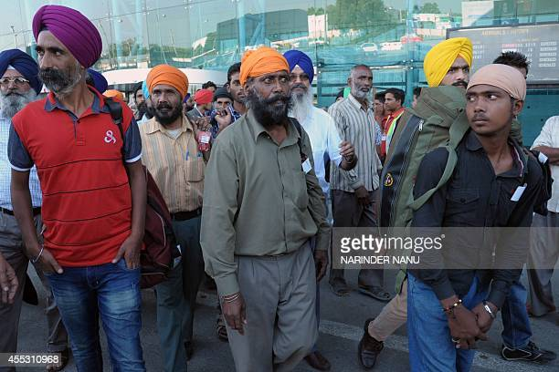 Indian Sikhs evacuated from flooding in Srinagar arrive at the airport in Amritsar on September 12 2014 Some 30 minority Sikhs rescued during floods...