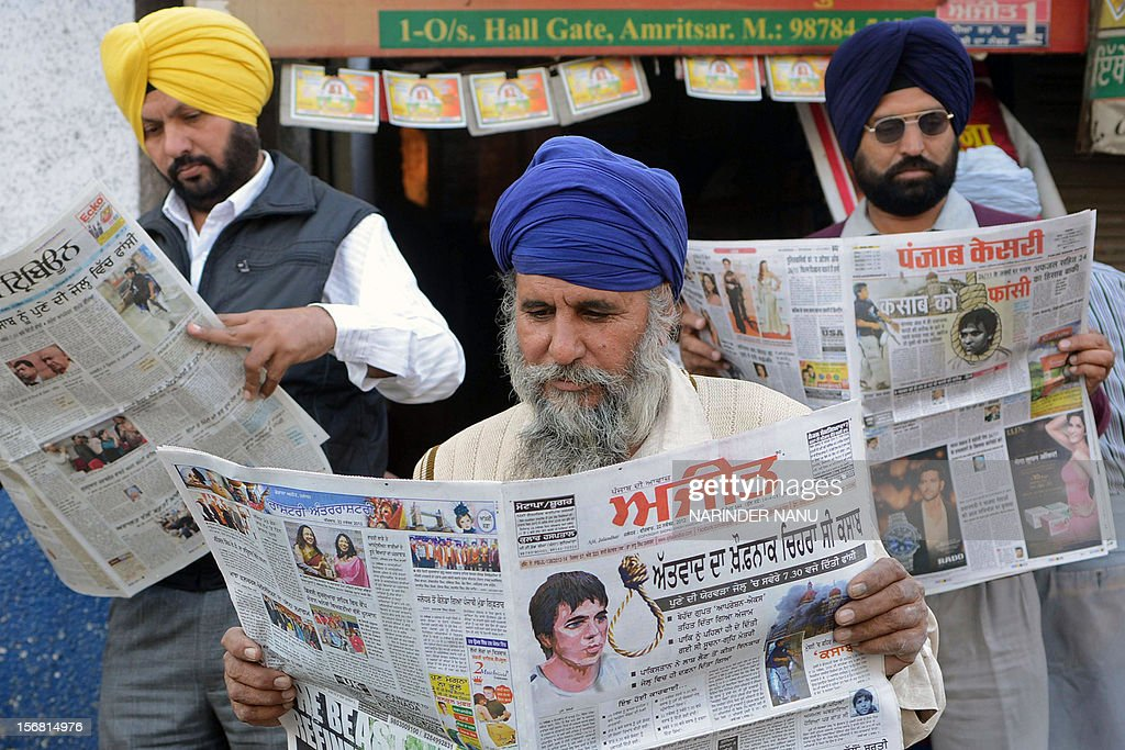 Indian Sikhs pose while reading newspapers displaying front page headlines on the execution of Mohammed Ajmal Amir Kasab who was the sole surviving...