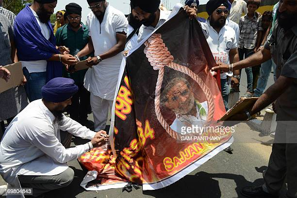 Indian Sikhs prepare to burn a poster depicting the image of Congress leader Sajjan Kumar during a rally seeking justice for the massacre of Sikhs...