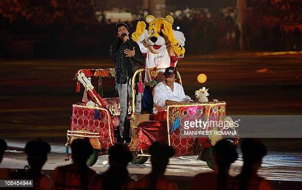 Indian singer Shaan performs with mascot Shera while riding in an autorickshaw during the Commonwealth Games closing ceremony at the Jawaharlal Nehru...