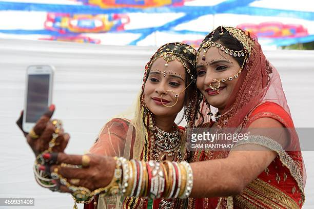 Indian sisters and brides from the Rabari Samaj community Rupal Desai and Rinku Desai take a 'selfie' photograph on a mobile phone before...