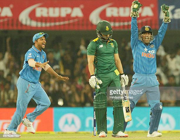 Indian skipper MS Dhoni and Suresh Raina celebrate after a wicket during the 2nd One Day cricket match against South Africa at Ushabai Holkar Stadium...