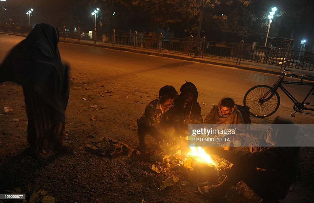 Indian slum dwellers warm themselves at a fire on the roadside in Siliguri on January 7, 2013. As thousands of homeless people sought places in temporary shelters, the unusual cold in throughout India has been attributed to dense fog which has obscured the sun and disrupted airports and trains, as well as icy winds from the snowy Himalayas to the north. AFP PHOTO/Diptendu DUTTA