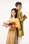 Indian small brother and sister in traditional wear standing with sweet laddu and gift boxes