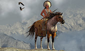 Two Bald Eagles fly near an American Indian with his paint horse on a tall cliff in a mountainous area.