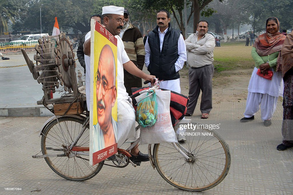 Indian social worker Sham Lal Gandhi carries a photograph of Mahatma Gandhi and transports a 'charkha' - spinning wheel - on his bicycle on the occasion of Martyr's Day in Amritsar on January 30, 2013, the 65th anniversary of Gandhi's assassination. Mahatma Gandhi was on the way to a prayer meeting in the Indian capital New Delhi when he was shot three times in the chest and head on January 30, 1948.