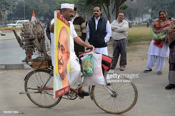 Indian social worker Sham Lal Gandhi carries a photograph of Mahatma Gandhi and transports a 'charkha' spinning wheel on his bicycle on the occasion...