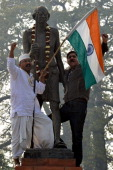 Indian social workers shout slogans after placing garlands on a statue of Mahatma Gandhi on Martyrs' Day in Amritsar on January 30 the 66th...