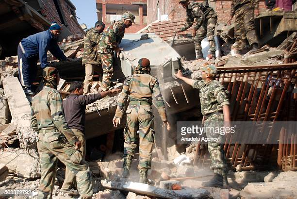 Indian soldiers and locals examine the debris of a damaged building after a strong earthquake in Imphal capital of the northeastern Indian state of...