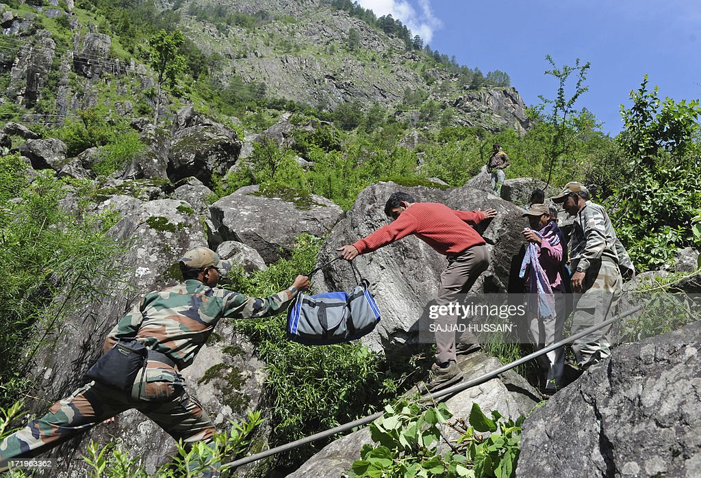 Indian soldiers assist stranded Indian pilgrims coming from Badrinath making their way down a mountain at Govindghat following flash floods in Uttarkhand state on June 30, 2013. Some 3,000 tourists and pilgrims remain missing in India's flood-ravaged north two weeks after the tragedy, but it is unclear how many of those have been killed, a top state official said June 30. AFP PHOTO/SAJJAD HUSSAIN