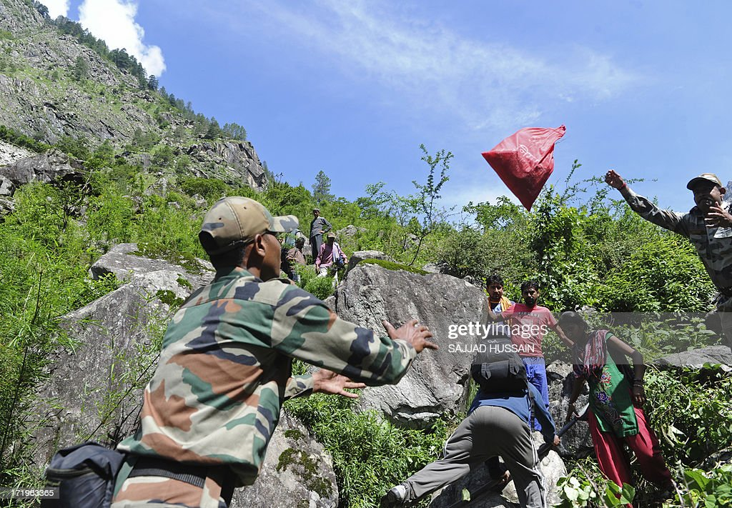 Indian soldiers assist stranded Indian pilgrims coming from Badrinath making their way down a mountain at Govindghat following flash floods in Uttarkhand state on June 30, 2013. Some 3,000 tourists and pilgrims remain missing in India's flood-ravaged north two weeks after the tragedy, but it is unclear how many of those have been killed, a top state official said June 30.