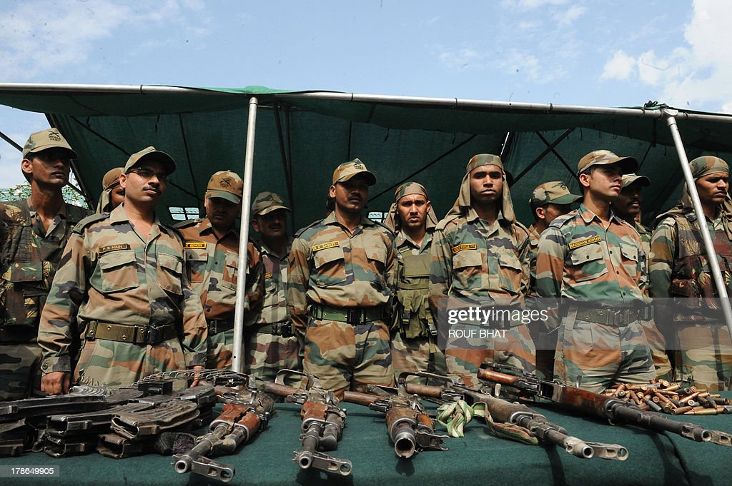Indian soldiers display weapons and ammunition, seized following a gunbattle, as a military base in Kangan on August 30, 2013. Indian police and troops killed five suspected rebels in an overnight gun battle August 30 in a forested area of northern Kashmir, triggering anti-India protests by local residents, police said. Police and an army contingent began a joint operation around midnight near the Najwan forests, 35 kilometres (20 miles) north of Srinagar, the summer capital of Indian-administered Kashmir. AFP PHOTO/Rouf BHAT