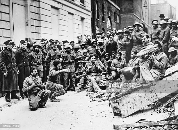 Indian soldiers entertain onlookers with traditional songs and music during their lunch hour London 27th May 1940
