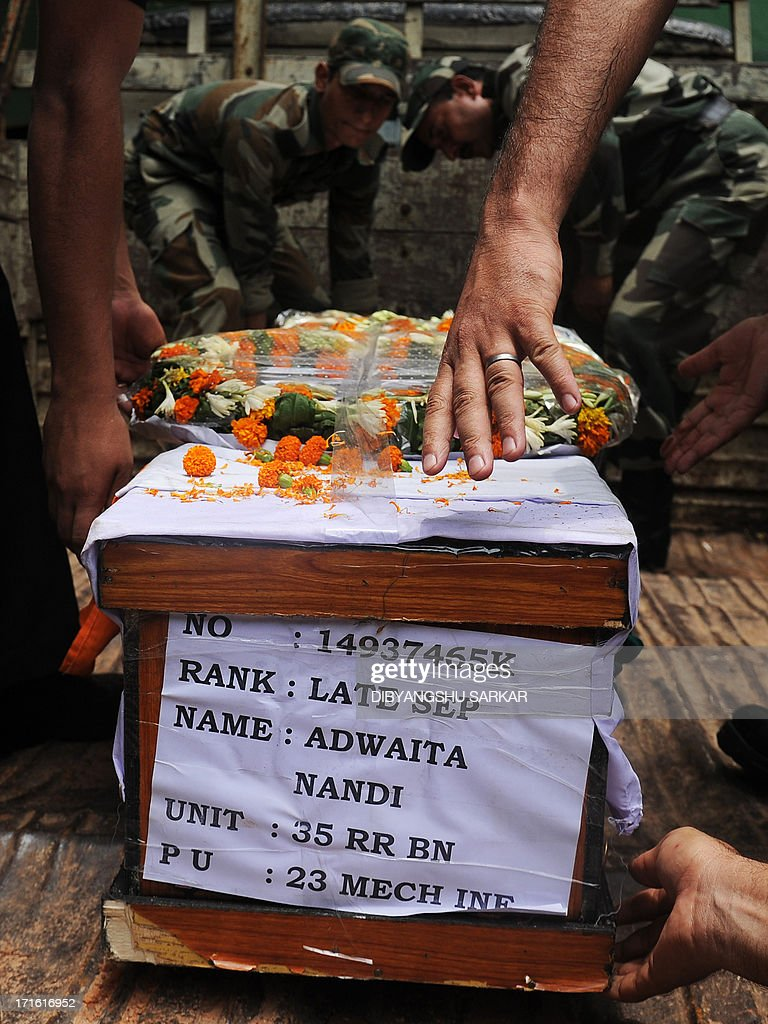 Indian soldiers handle a coffin bearing the mortal remains of fallen comrade Late Sepoy Adwaita Nandi, who was who was killed in Srinagar on June 24 with seven other soldiers, during a ceremony in Kolkata on June 27, 2013. The fallen soldier's widow, 22-year old Piu Nandi, commited suicide following the news of her husband's death. Militants staged an attack June 24 on a troop convoy on the outskirts of Srinagar, killing eight soldiers and wounding 13 others on the eve of a visit by Prime Minister Manmohan Singh. AFP PHOTO/ Dibyangshu SARKAR