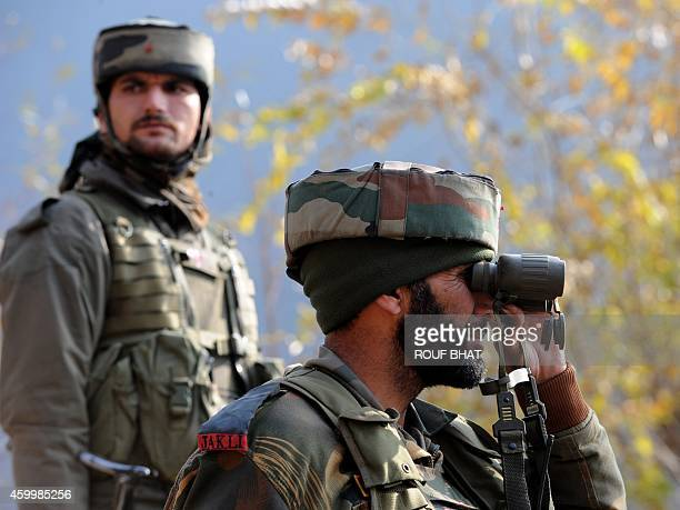 Indian soldiers look on from their position by a road overlooking army barracks following an attack by militants on the camp in Gingal Uri some 90...