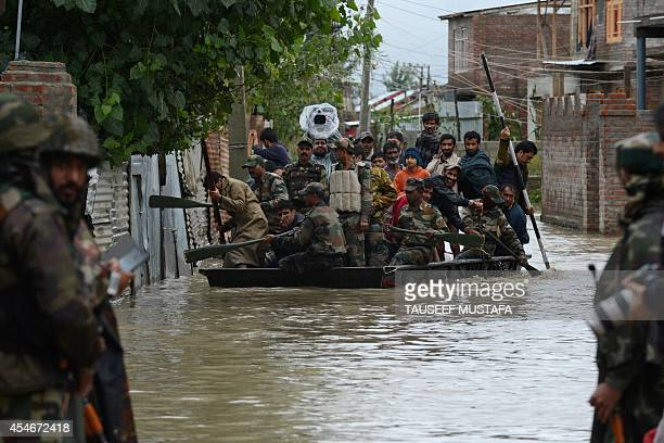 Indian soldiers paddle a raft as they assist Kashmiri residents during flood rescue operations in the outskirts of Srinagar on September 5 2014...